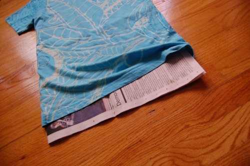Place a few newpaper sheets inside the t-shirt to prevent applied bleach from leaking through to the other side of the garment